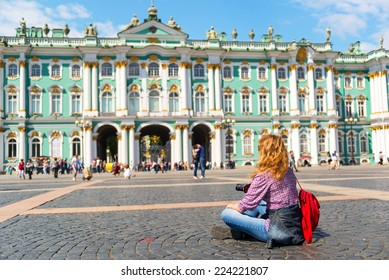 Young woman relax in front of the Winter Palace in Saint Petersburg, Russia. It is one of the main tourist attractions of St Petersburg. People visit the Palace Square in St Petersburg in summer.