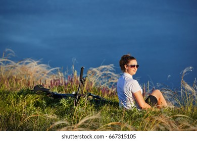 Young woman relax on a beach during bicycle journey