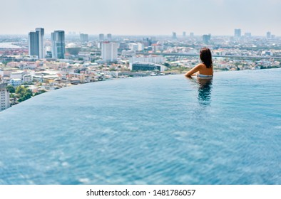 Young woman relax on the edge of the roof top swimming pool. Summer vacation concept