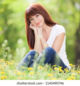 Young woman relax in the park with flowers. Beauty nature scene with colorful background, trees and flowers at summer season. Outdoor lifestyle. Happy smiling woman sitting on green grass