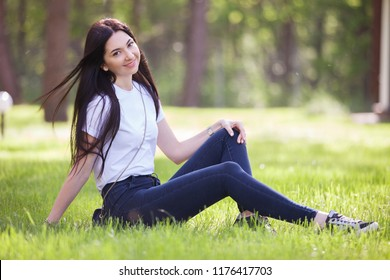 Young woman relax in the park on green grass. Beauty nature scene with colorful background, trees at summer season. Outdoor lifestyle. Happy smiling woman sitting on green grass