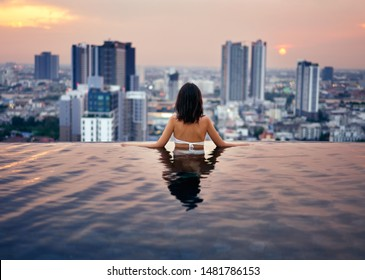 Young woman relax in swimming pool on roof top during amazing sunset and enjoy city view. Summer vacation and holidays concept