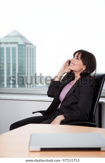 Young Woman Relaxed In Chair And Talking On Cell Phone In Office.