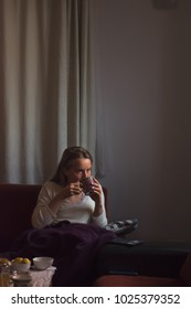 The young woman relaxes at home and drinks tea in the winter