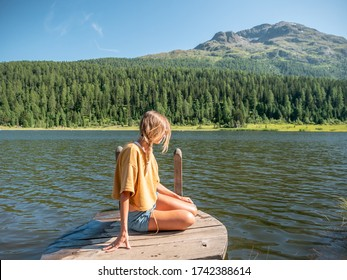 Young woman relaxes on lake pier in Summer enjoys the freshness from the mountains. Girl sitting by an alpine lake in Switzerland