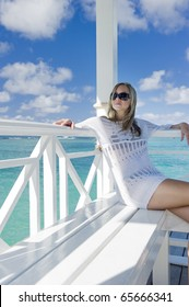 A young woman relaxes on a white Caribbean porch
