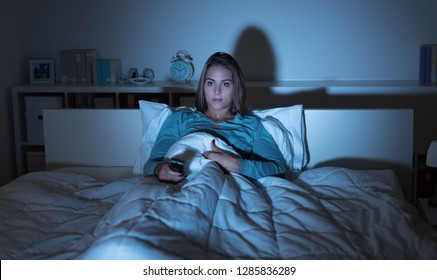 Young woman relaxing in bed late at night and watching tv, she is holding a remote control