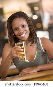 Young woman relaxing with a beer at a bar