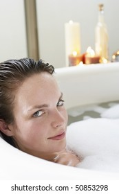 Young woman relaxing in bubble bath, close-up