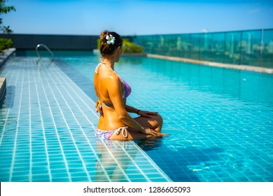 Young Woman relaxing by the side of the infinity pool