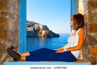 Young woman relaxing by window frame and looking view  in Santorini island Greece
