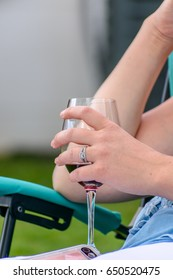young woman relaxing in chair in backyard with a glass of red wine