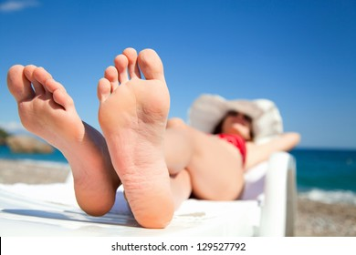Young woman relaxing in chaise longue on the beach
