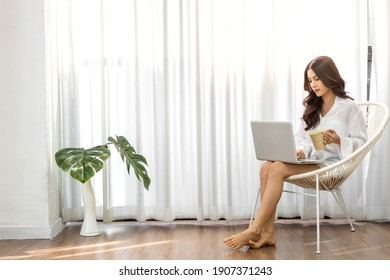 Young woman relaxing and drinking cup of hot coffee or tea using laptop computer on chair.woman checking social apps and working.Communication and technology concept