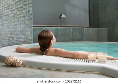 Young woman relaxing at the edge of a hot pool at spa center