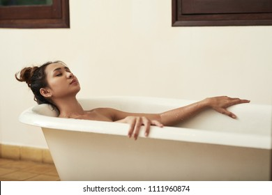 Young woman relaxing with eyes closed in bath