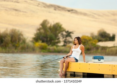 A young woman relaxing and fishing from a dock on a small lake in Northern California on a warm summer evening.