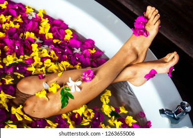 Young woman relaxing in flower bath,organic skin care, luxury spa hotel.legs close up care top view.view from above sexy foot feet girl wellness treathment red,yellow, pink flowers petals in milk bath