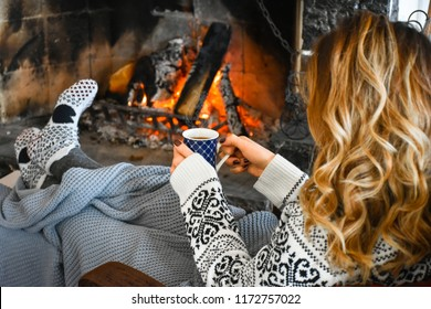 Young woman relaxing in front of cozy fireplace and warming up her feet in woolen socks in country house. Woman holding mug of tea or coffee. Winter or autumn vacation. Christmas holidays concept.