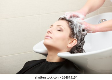 Young woman relaxing in hairdressing beauty salon. Hairstylist washing hair female client with shampoo.