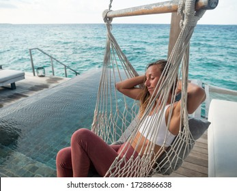Young woman relaxing in hammock in private pool villa in luxury tropical destination. Vacation relax people enjoying sea