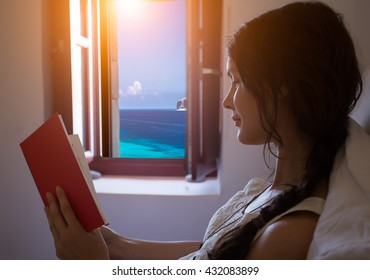 Young woman relaxing at home enjoying reading the book in front of window with the sea view.