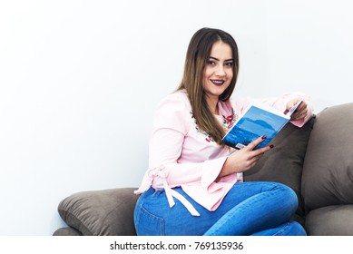 Young woman relaxing at home and reading a book