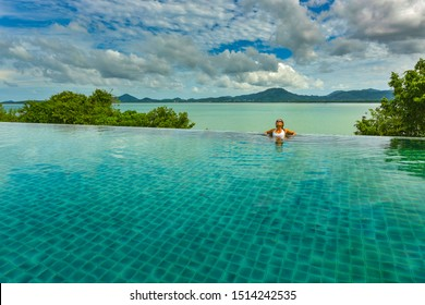 Young woman relaxing in the infinity swimming pool at luxurious resort in Phuket Thailand