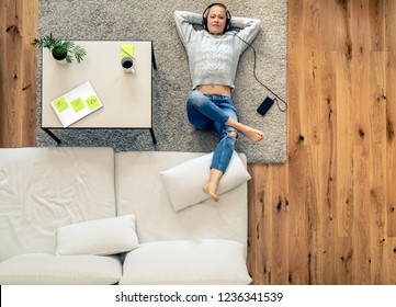 Young woman relaxing and listening to music from smart phone using headphones. Home office break with laptop computer and coffee waiting on a table.