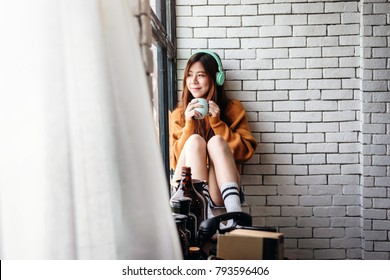 Young Woman Relaxing with Music From Headphone in Cozy House, Enjoying with Morning Sunshine from Window and Hot Coffee
