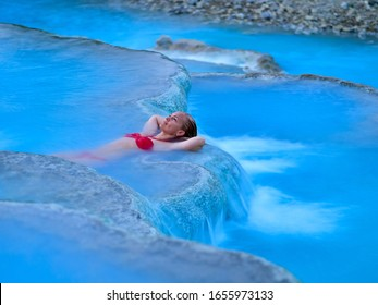 young woman relaxing at natural spa with waterfalls and hot springs at Saturnia thermal baths, Grosseto, Tuscany, Italy