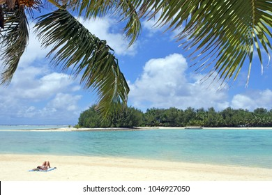 Young woman relaxing on the beach in Muri Lagoon in Rarotonga, Cook Islands. Real people. Copy space