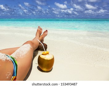 Young woman relaxing on the beach with his legs crossed on a coco. Girl resting in the Bahamas. photo girls feet on the coast of Jamaica. View of the tropical sea beach with the Caribbean islands.