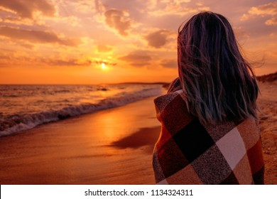 Young woman relaxing on coast near the sea at sunset in summer.