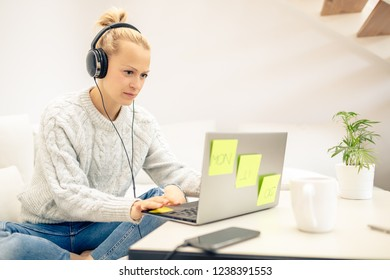 Young woman relaxing on couch and listening to music using smart phone and headphones. Working at home office from sofa in warm cosy sweater.