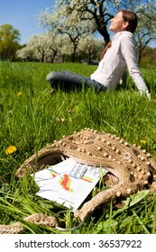 Young woman relaxing on a meadow with medicine in foreground.