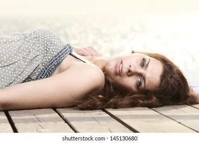 young woman is relaxing on the pier in the morning, summer holiday