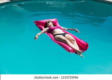 Young woman relaxing on a pink raft in an outdoor swimming pool in a bikini and aviator sunglasses. Enjoying the sun, lounging in a swimming pool arms extended floating in a pool in the sun.