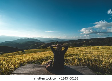 Young woman relaxing on rice field, mountain view, Vacation Outdoors landscape Concept