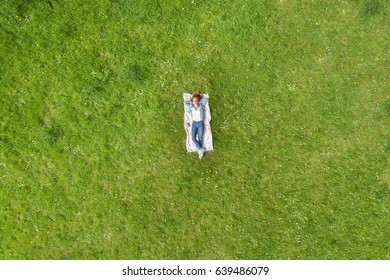 Young woman relaxing on a rug on the grass viewed from high overhead as a diminutive person in the center of a field of green grass