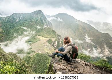 Young woman relaxing on the top of majestic Huayna Picchu mountain, watching Machu Picchu
