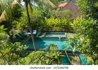 Young woman relaxing in outdoor swimming pool surrounded with lush tropical greenery of Ubud, Bali. Luxury tropical retreat vacation concept.