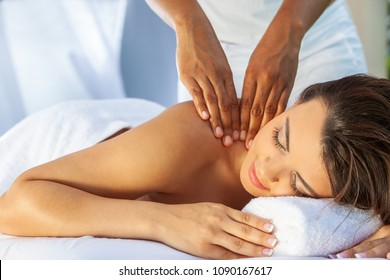 A young woman relaxing outside at a health spa while having a massage