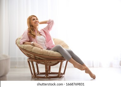 Young woman relaxing in papasan chair near window at home