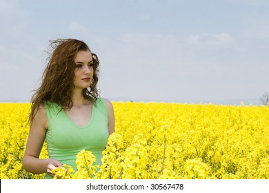 young woman relaxing in the rapeseed flower field