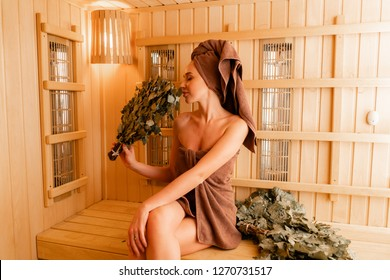 Young woman relaxing in a sauna dressed in a towel. Interior of new Finnish sauna, infrared panels for medical procedures, classic wooden sauna. oak broom