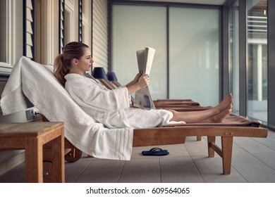 Young woman relaxing at a spa after a pampering treatment sitting on a day bed on a patio reading a newspaper in a white bathrobe
