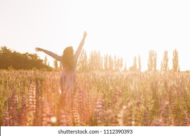 Young woman relaxing in summer sunset sky outdoor. People freedom concept