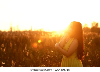 Young woman relaxing in summer sunset sky outdoor. People freedom style. Fashion Lifestyle, Portrait of Beautiful Young Woman Backlit at Sunset Outdoors. Soft warm sunny colors.
