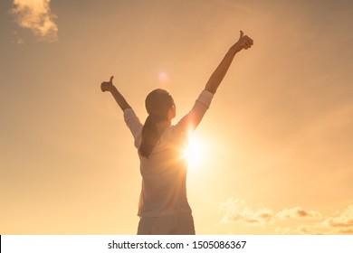 Junge Frau entspannend im Sommer Sonnenuntergang Himmel draußen. Menschen Freiheit, Gefühl, positiver Lebensstil.
